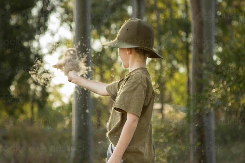 Young boy waving a bulrush seed head in the wind - Australian Stock Image