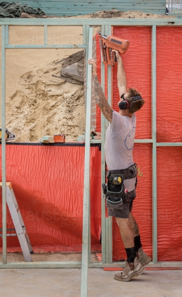 Young builder using nail gun on timber frame on residential construction site - Australian Stock Image