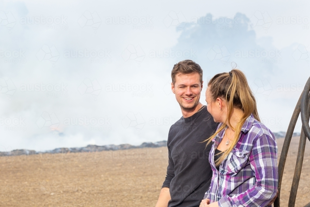Young couple looking at each other outdoors with smoky background - Australian Stock Image