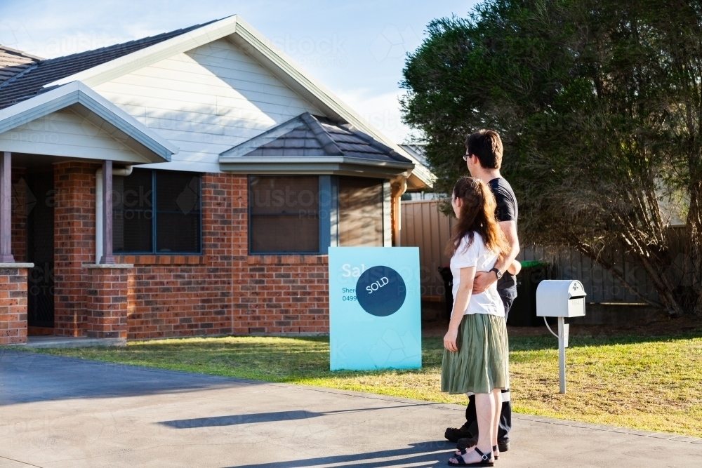 Young couple looking at front of suburban house with sold sign - Australian Stock Image