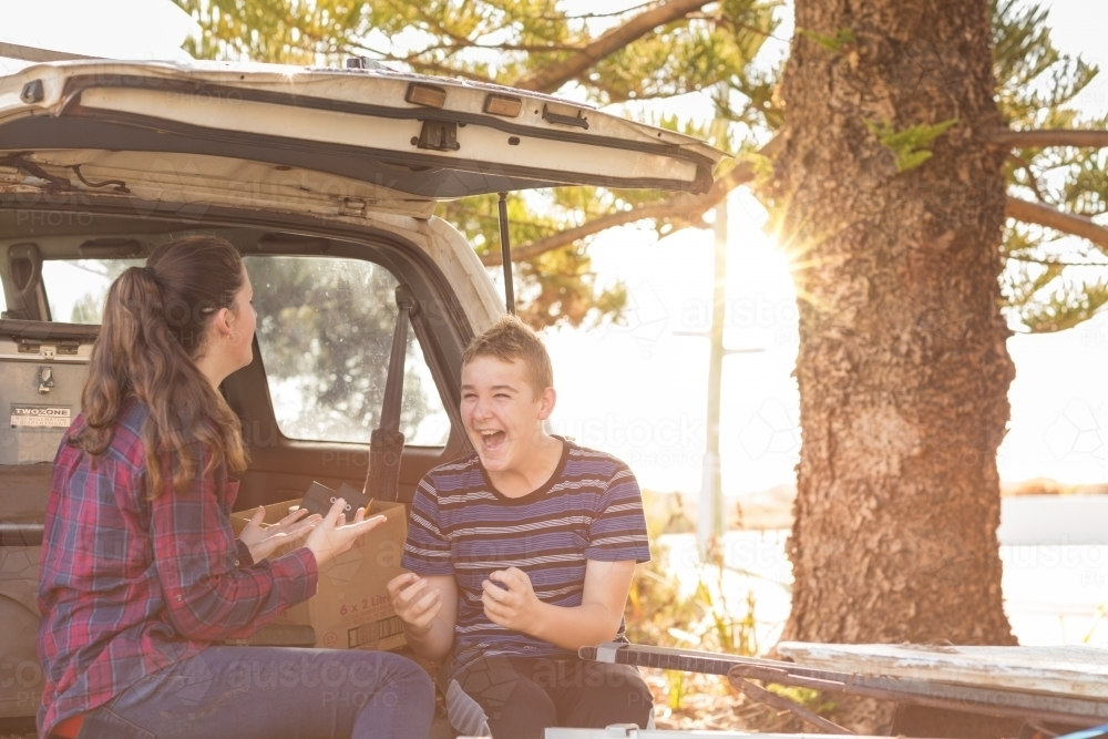 Young couple sitting on tailgate of 4WD vehicle - Australian Stock Image