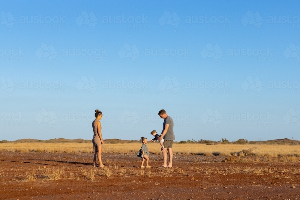 young family of four in the Pilbara landscape with big blue sky - Australian Stock Image