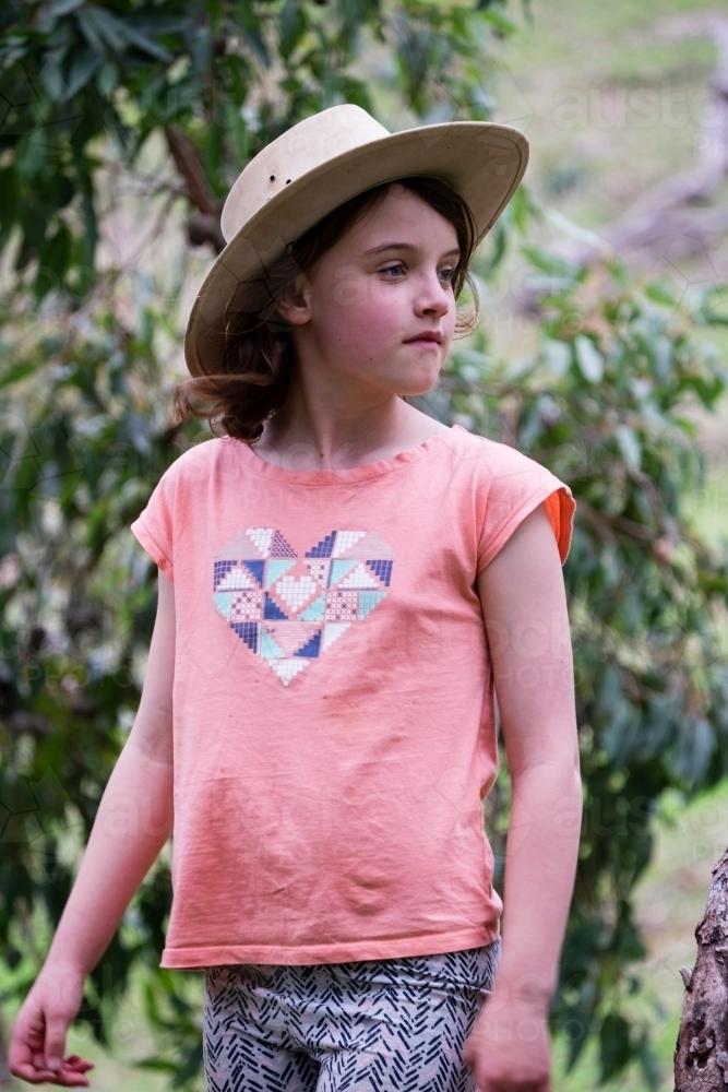 0e2e6a44972 Young farmer girl wearing akubra hat and looking away from camera in bush  environment - Australian