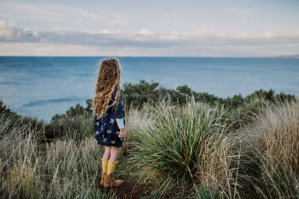 Young fashionable girl standing on a cliff top looking out to the ocean - Australian Stock Image