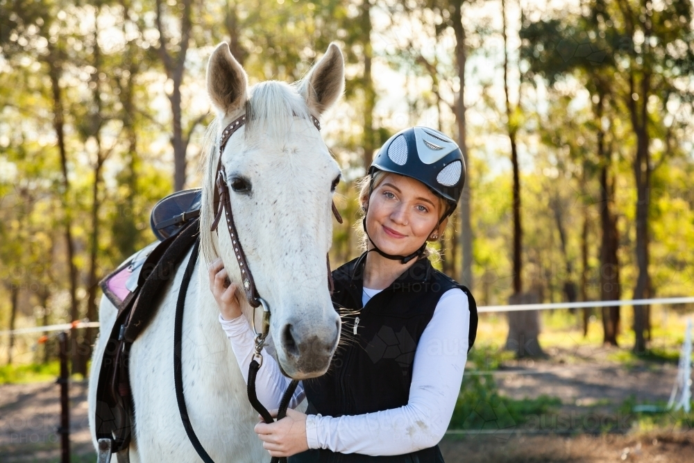 Young female horsewoman with her horse wearing a riding helmet for safety - Australian Stock Image