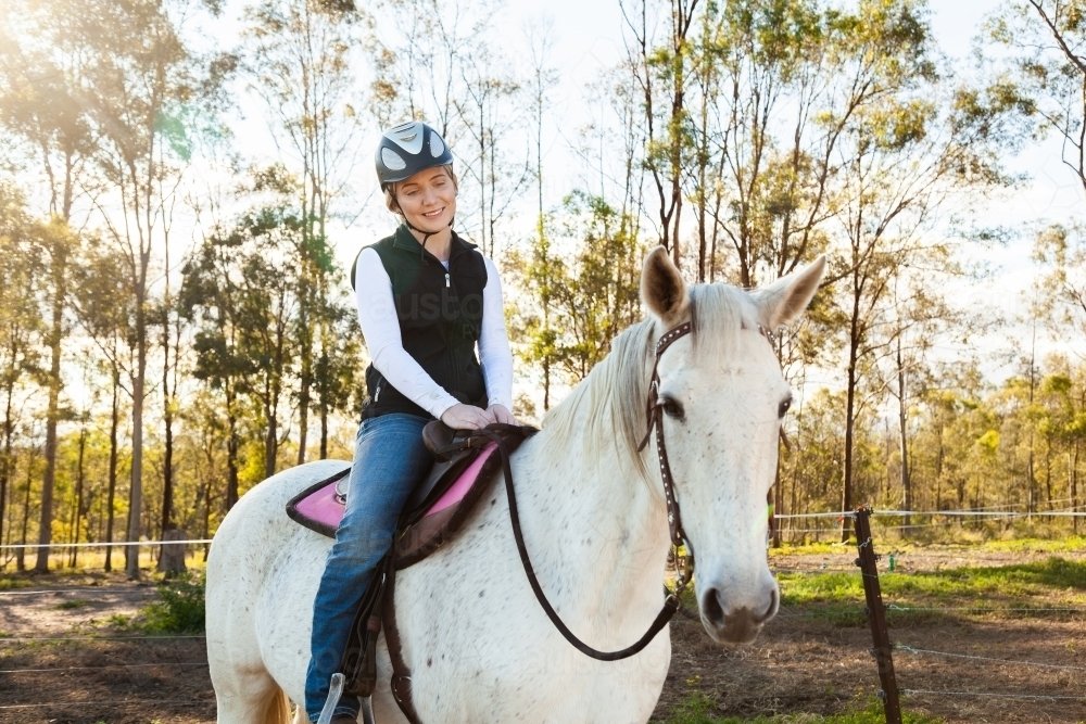 Young female rider on her horse wearing a riding helmet for safety - Australian Stock Image