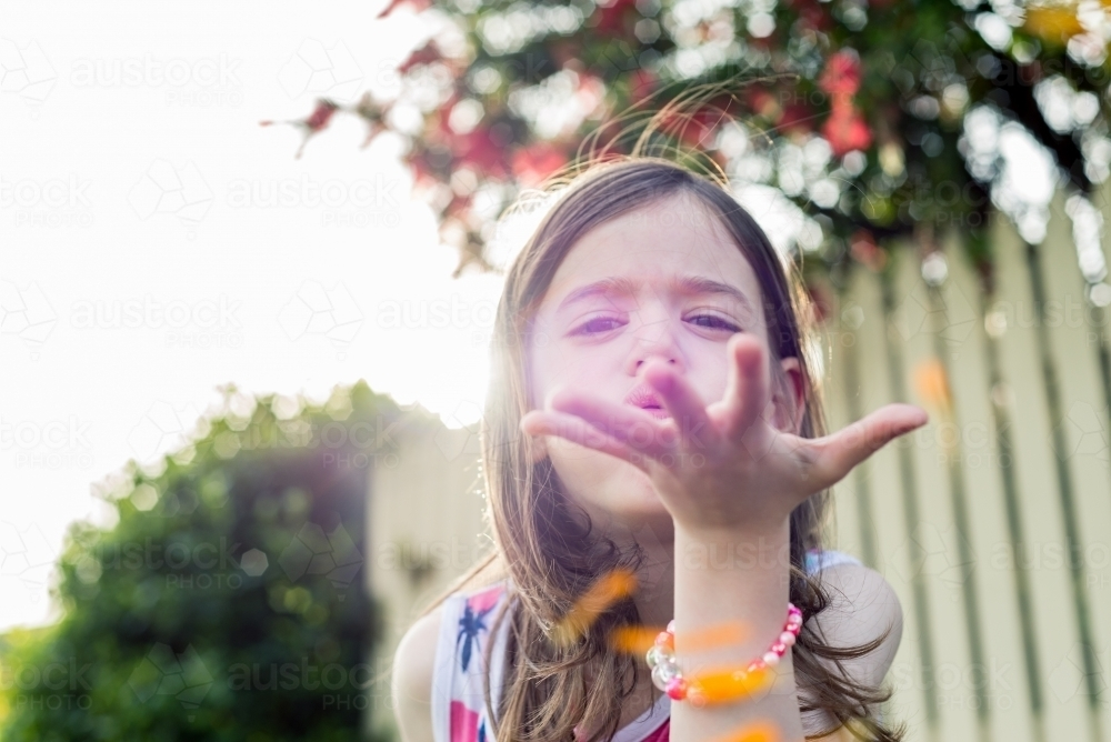 Young girl blowing orange flower petals from her hand - Australian Stock Image