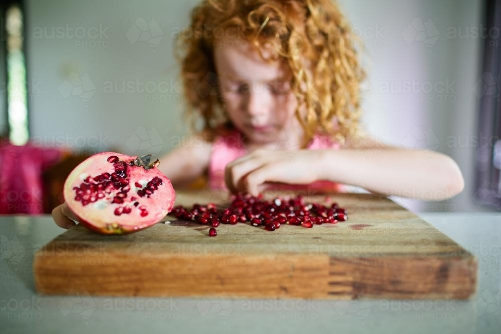 Young girl collecting pomegranate seeds in the kitchen - Australian Stock Image