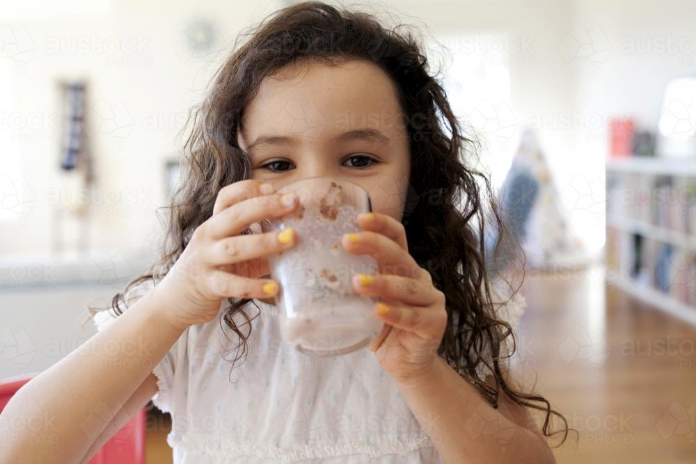 Young girl drinking chocolate milk smiling behind glass - Australian Stock Image