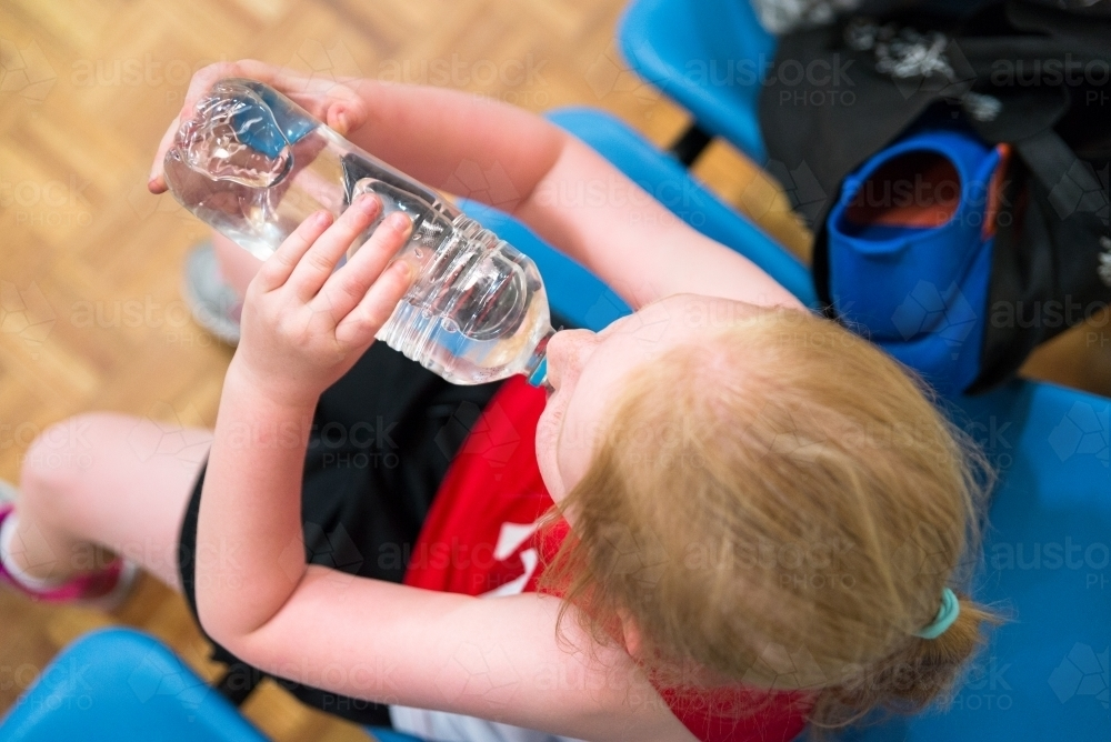Young Girl Drinking Water On Sideline Sports Game, Top View - Australian Stock Image