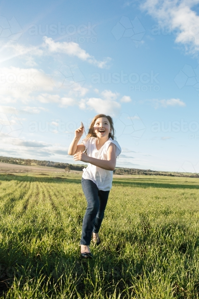 Young girl flying a paper aeroplane in a green farm paddock - Australian Stock Image