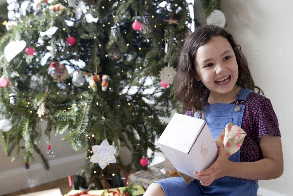 Young girl happy and smiling after opening gift in front of Christmas tree - Australian Stock Image