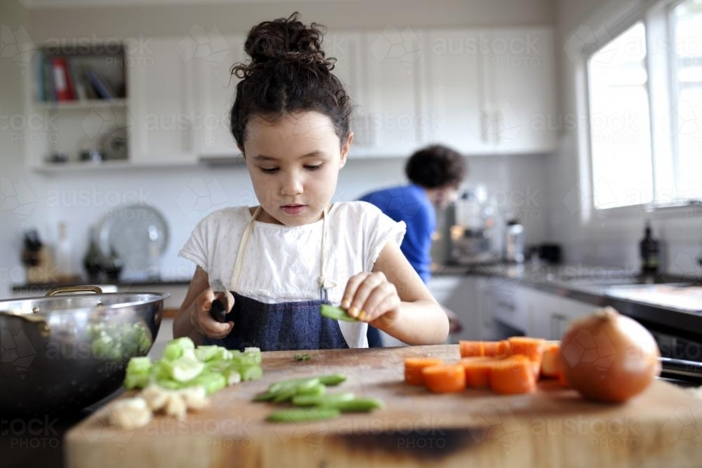 Young girl helping chop vegetables in kitchen - Australian Stock Image