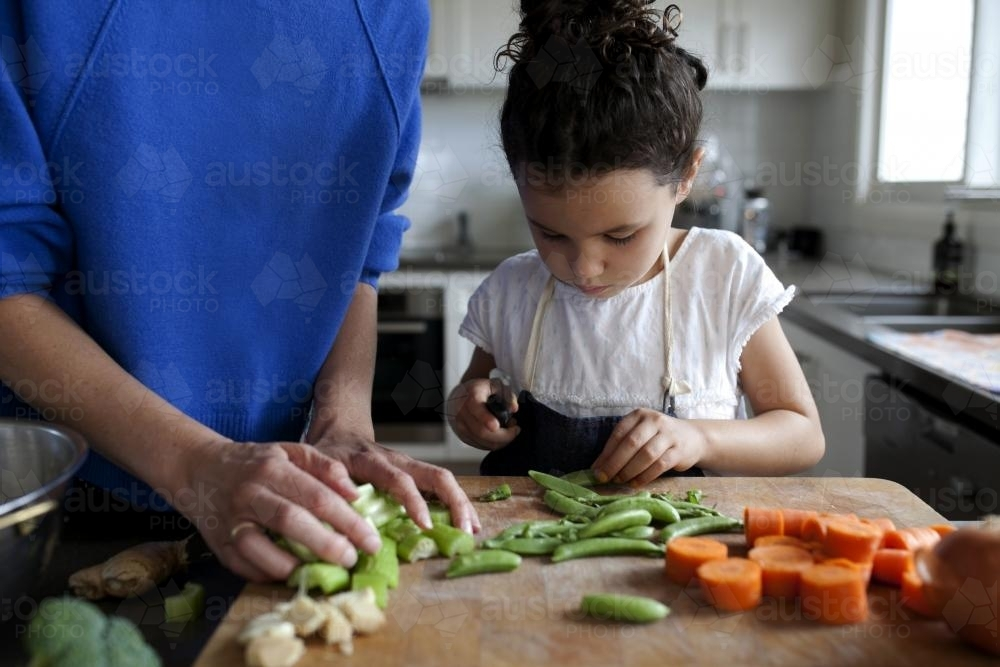 Young girl helping to chop vegetables - Australian Stock Image