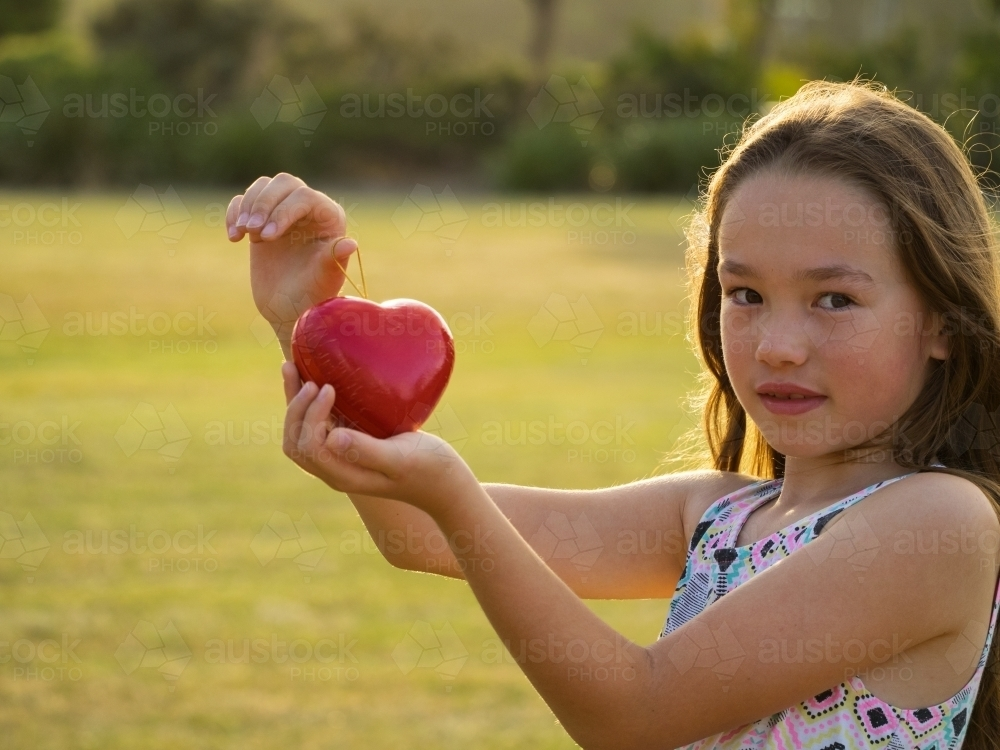 Young girl holding a red love heart. Be my Valentine - Australian Stock Image