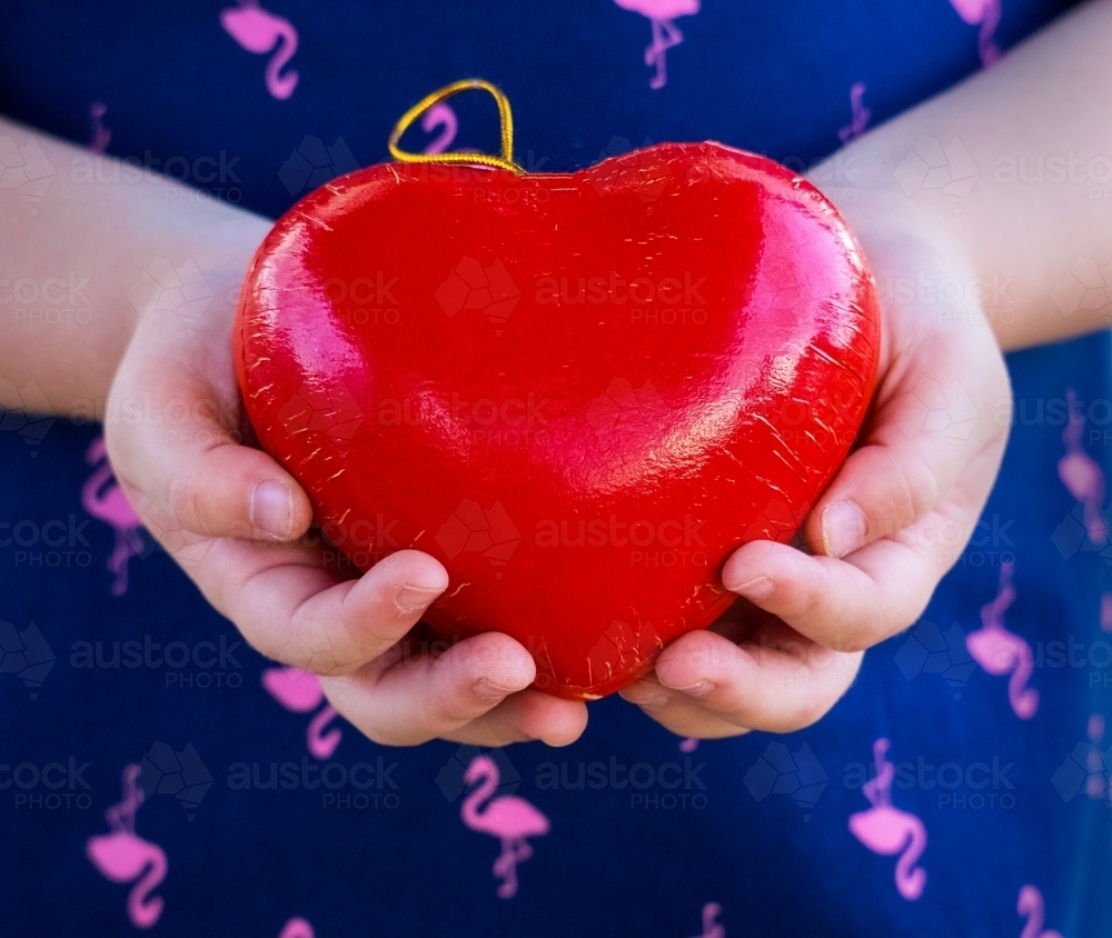 Young girl holding a red love heart in her hands Valentine - Australian Stock Image