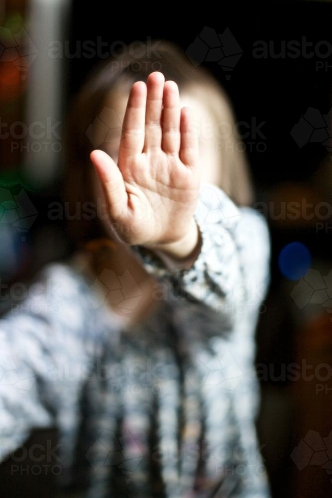 Young girl holding her hand up to the camera to say stop - Australian Stock Image