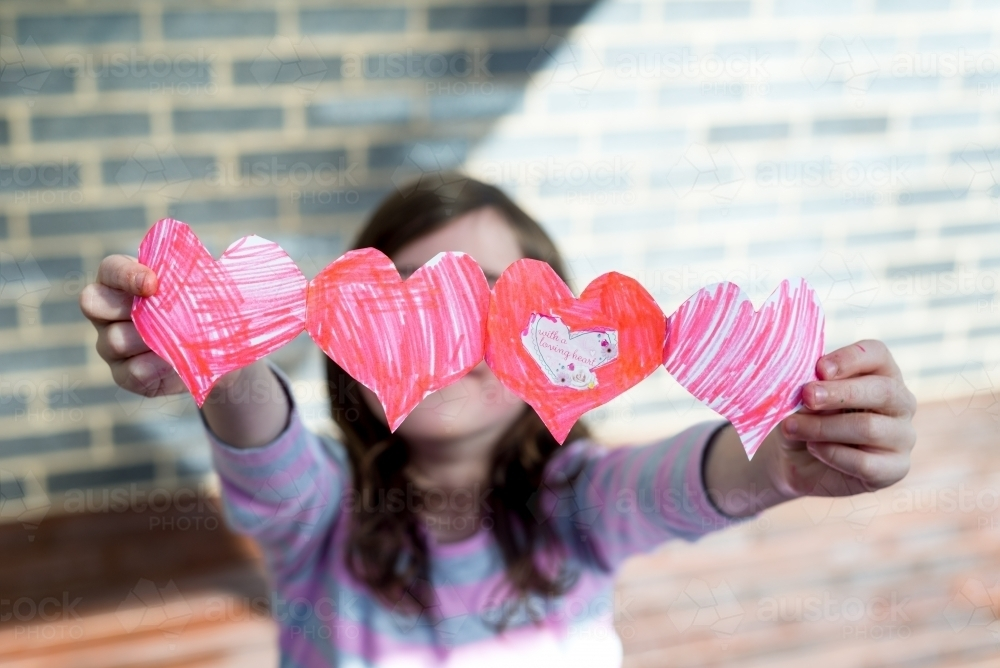 Image of Young girl holding out hand made cut out paper hearts ...