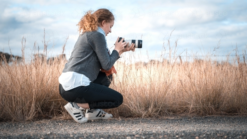 Young girl in profile kneeling taking picture of landscape - Australian Stock Image