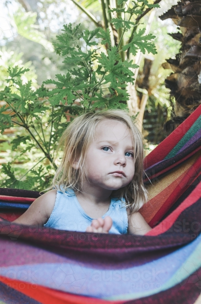 Young girl in rainbow hammock - Australian Stock Image