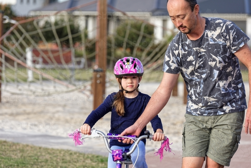 Young girl learning to ride her bike with her dad in the park - Australian Stock Image