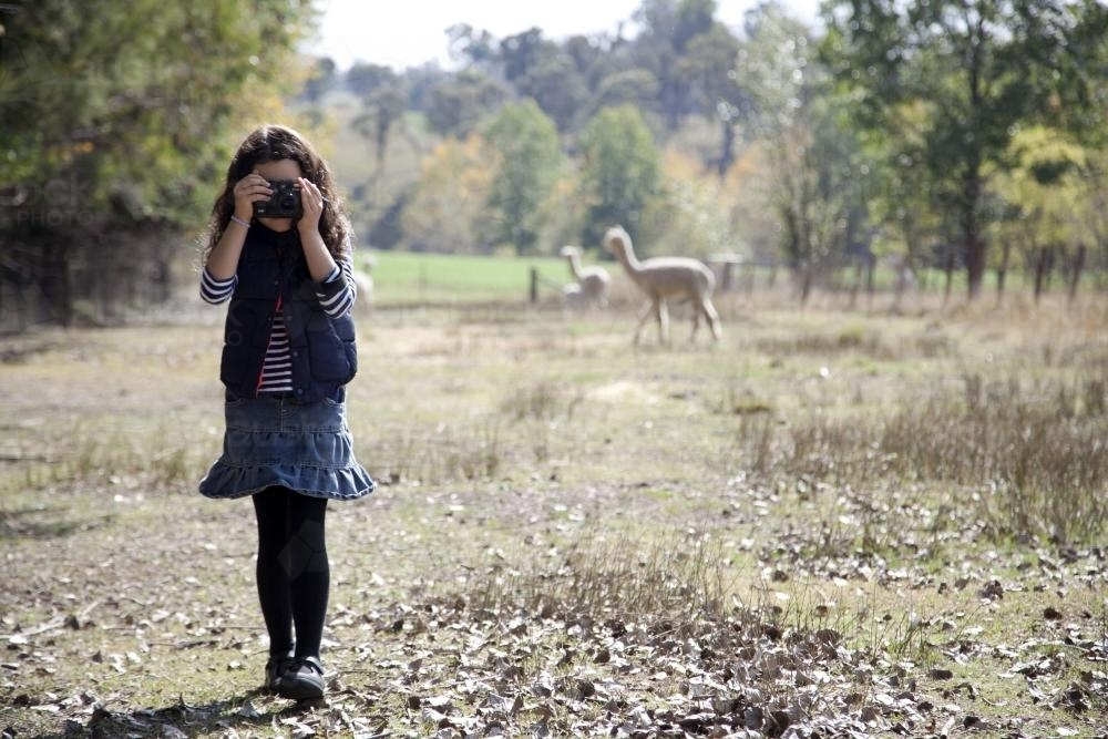 Young girl outside on a farm using a digital camera - Australian Stock Image