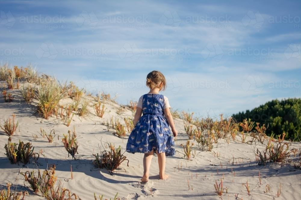 Young girl playing in sand dunes - Australian Stock Image