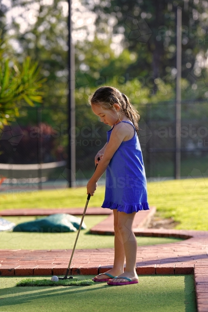 Young girl playing mini golf or putt-putt holding golf iron - Australian Stock Image