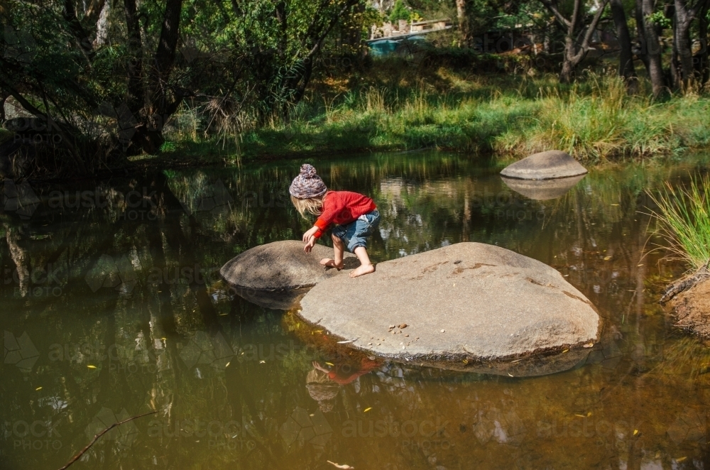 Young girl playing on rocks in a creek - Australian Stock Image