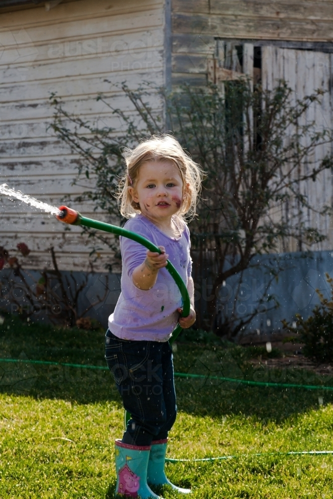 Young girl playing with a hose and water in the backyard - Australian Stock Image