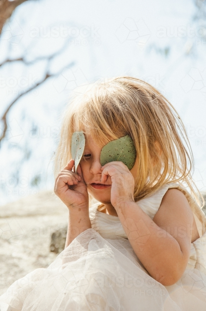 Young girl playing with gumleaves - Australian Stock Image