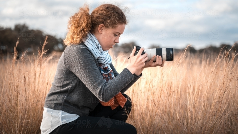 Young girl profile holding camera - Australian Stock Image