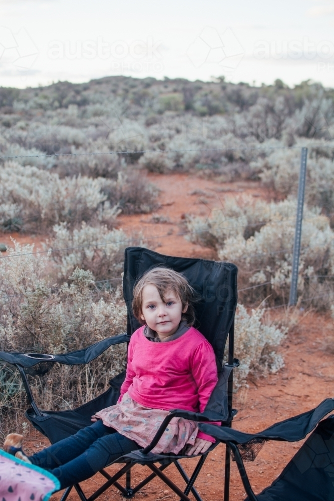Young girl sitting in camper chair - Australian Stock Image