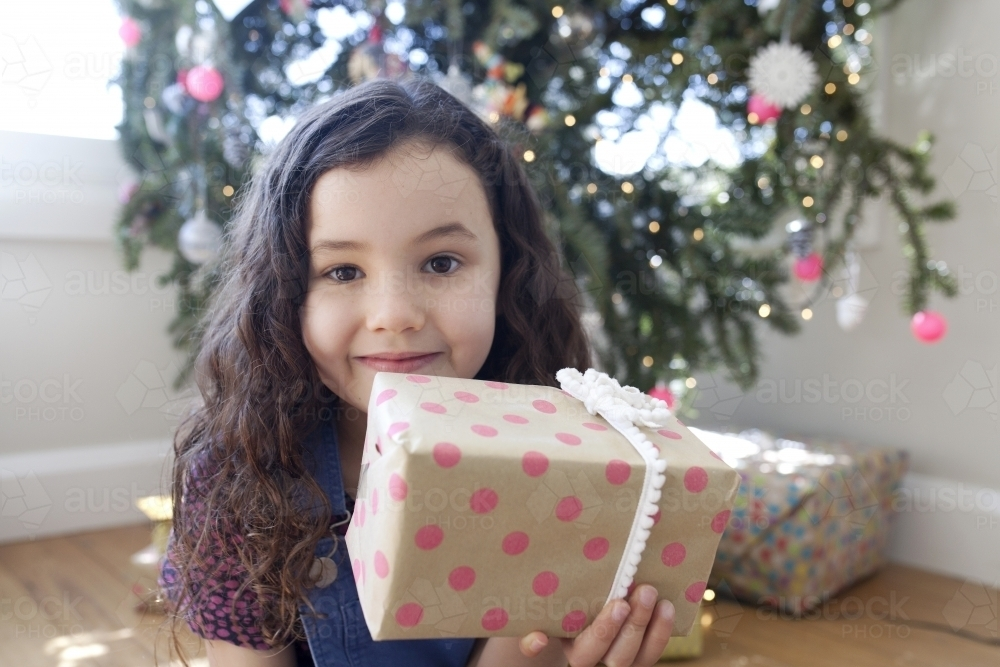 Young girl sitting in front of christmas tree holding a present up in front of her face - Australian Stock Image