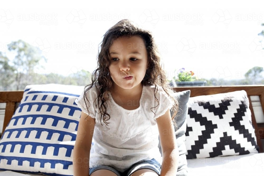 Young girl sitting on couch with cushions - Australian Stock Image