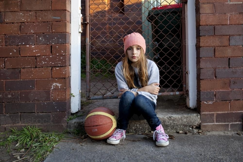 Young girl sitting on sidewalk with basketball - Australian Stock Image