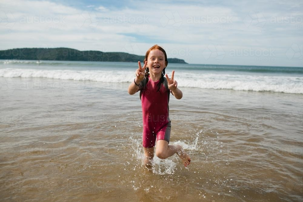 Young girl smiling in the water at the beach - Australian Stock Image