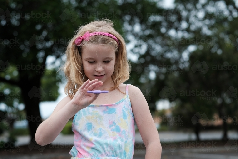 Young girl smiling playing with fidget spinner toy - Australian Stock Image