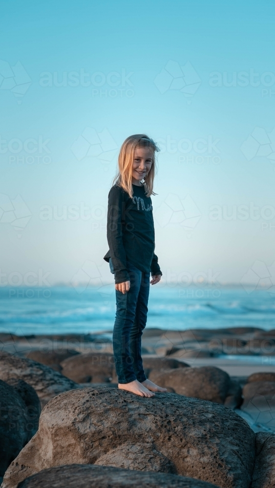 Young girl standing on rock at the beach - Australian Stock Image