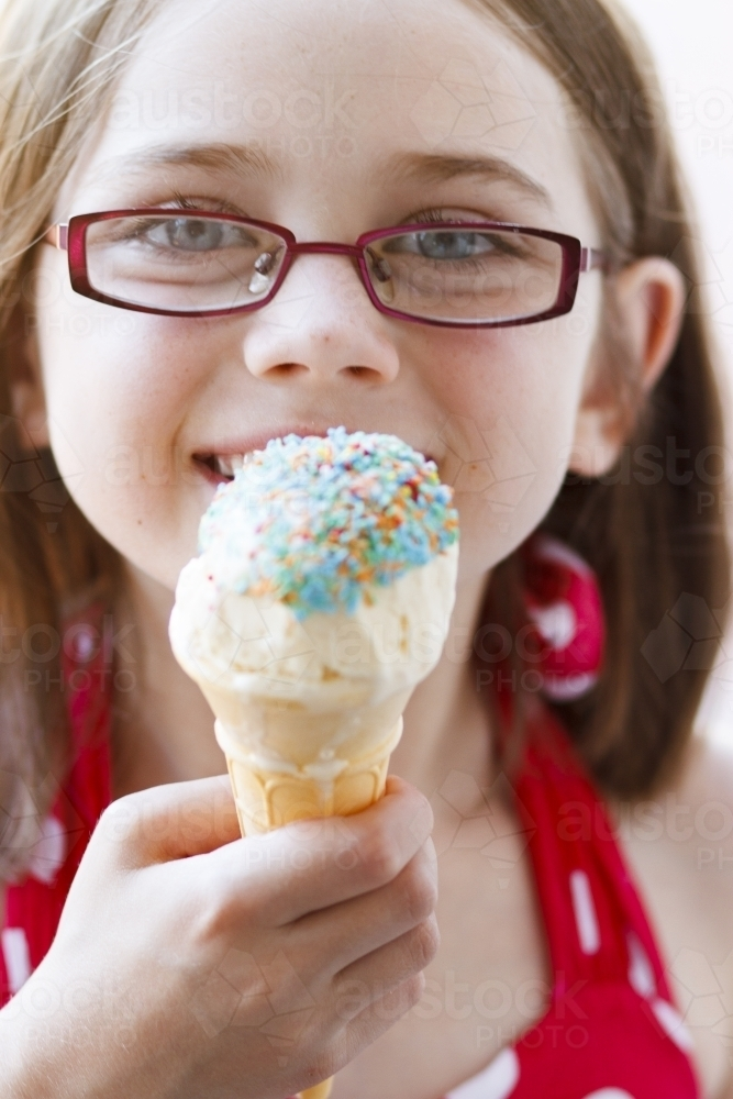 Young girl with ice cream covered in sprinkles - Australian Stock Image