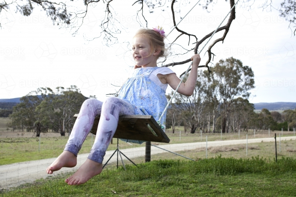 Young happy girl on tree swing in country backyard - Australian Stock Image