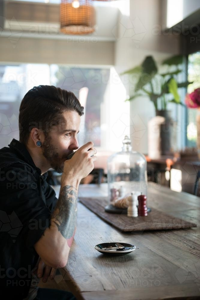 Young hipster man drinking coffee in a modern cafe - Australian Stock Image
