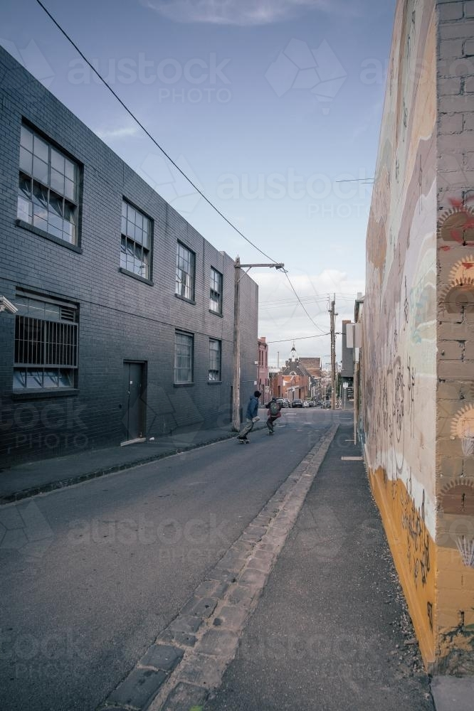 Young hipster on a skateboard in alley - Australian Stock Image