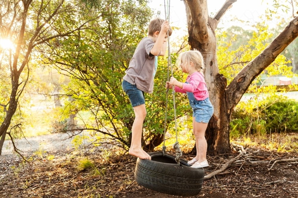 Young kids playing together on tire swing in backyard - Australian Stock Image