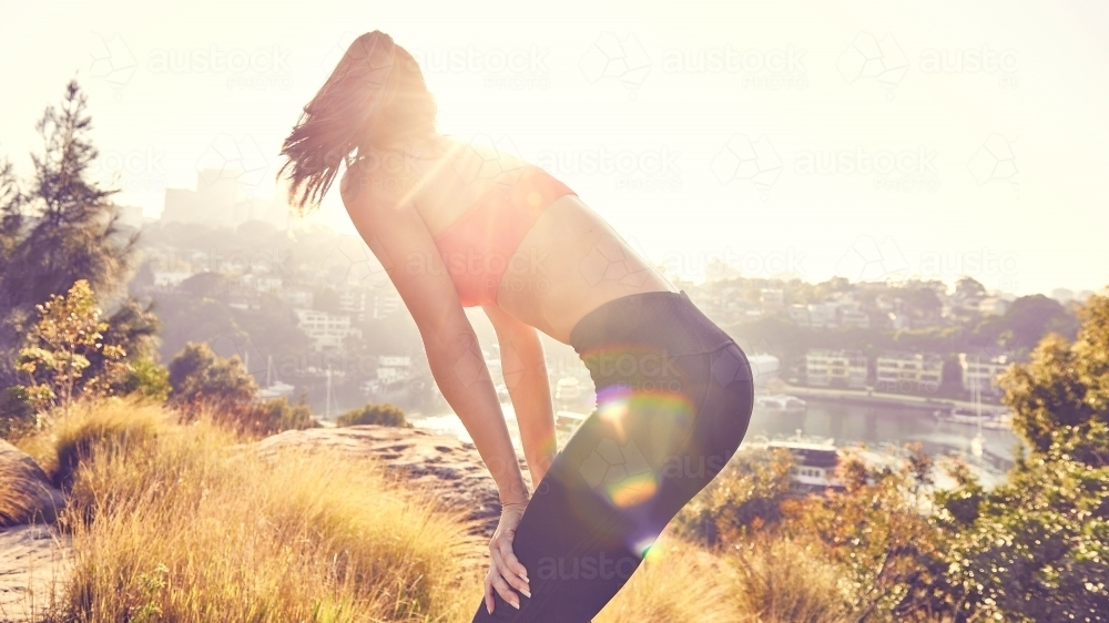 Young lady resting after a run looking at the view - Australian Stock Image