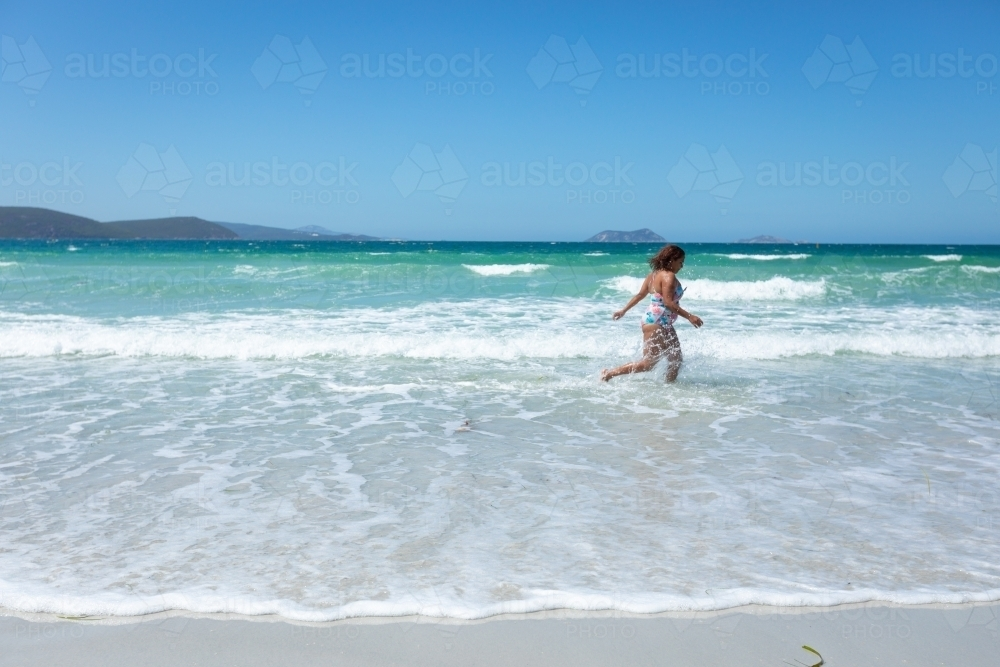 young lady running through the shallows on Middleton Beach - Australian Stock Image