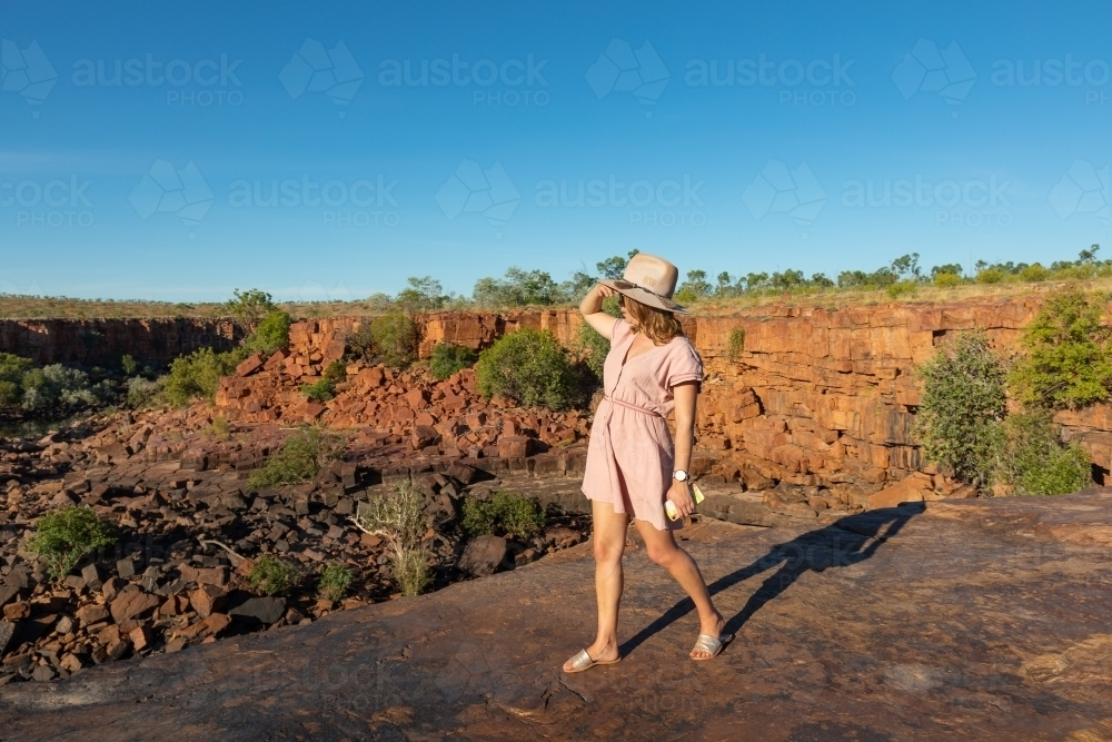 young lady tourist holding her hat while walking on rocky ledge in the Kimberley - Australian Stock Image