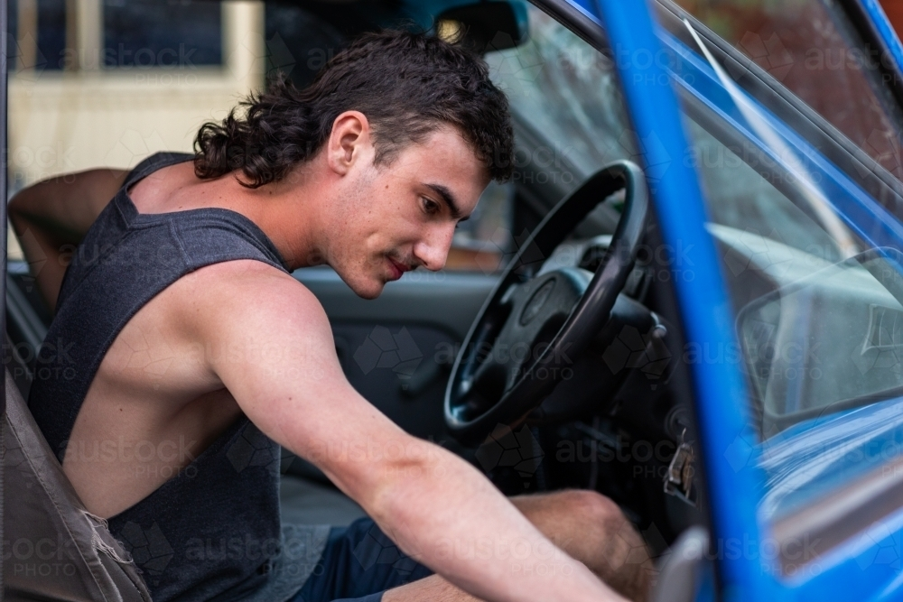 young man in driver's seat pulling car door closed - Australian Stock Image