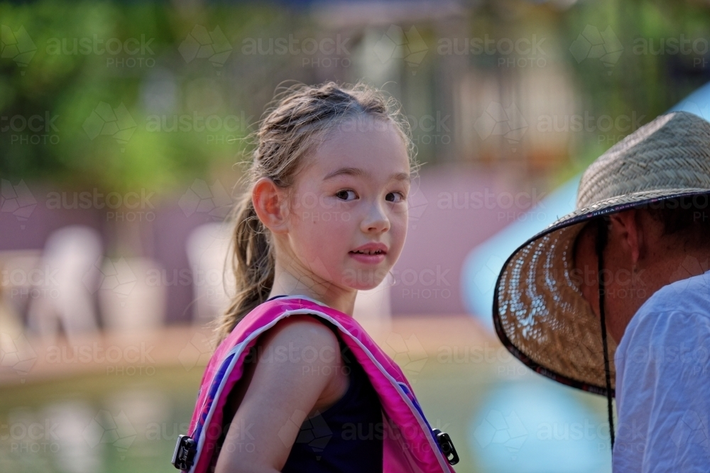 Young mixed race girl in swimming pool with vest on looking back over shoulder - Australian Stock Image