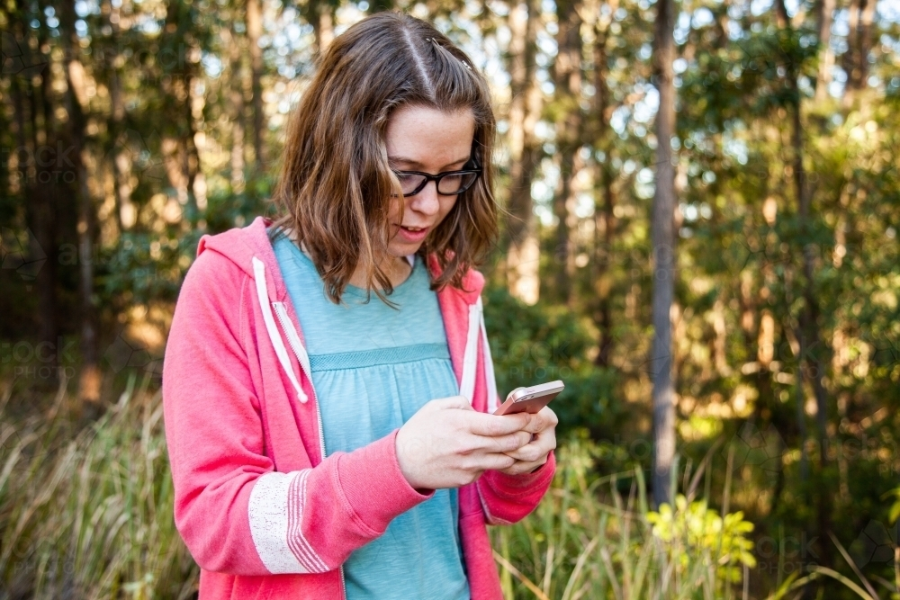 Young person holding mobile phone texting in forest - Australian Stock Image
